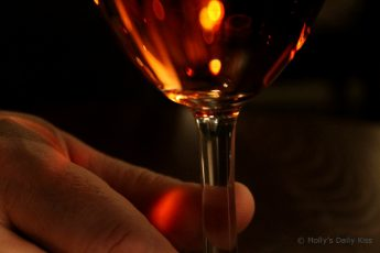 fingers holding stem of wine glass macro shot