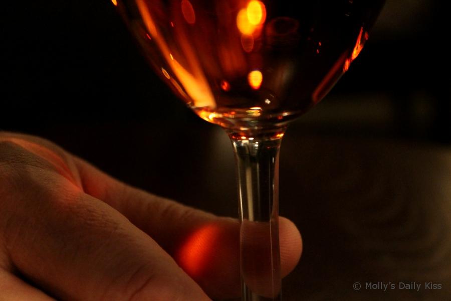 fingers holding stem of wine glass macro shot