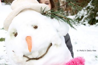 building a snowman with a pink scarf