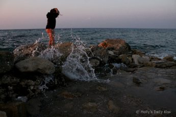 waves over the rocks around a little girl