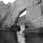 Hole in the cliff wall surrounded by sea
