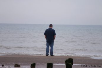 man walking on empty beach facing out to sea