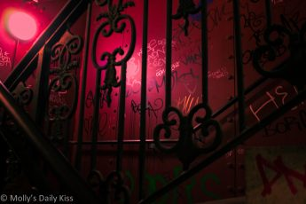 Graffiti in a stairwell with pink light
