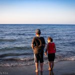 Siblings standing on the shore