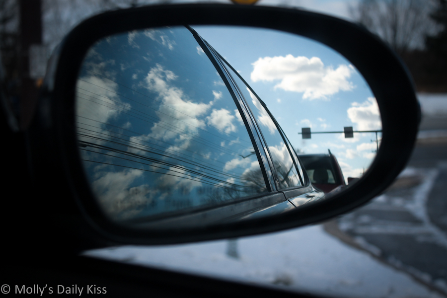 Blue sky and clouds in the car wing mirror