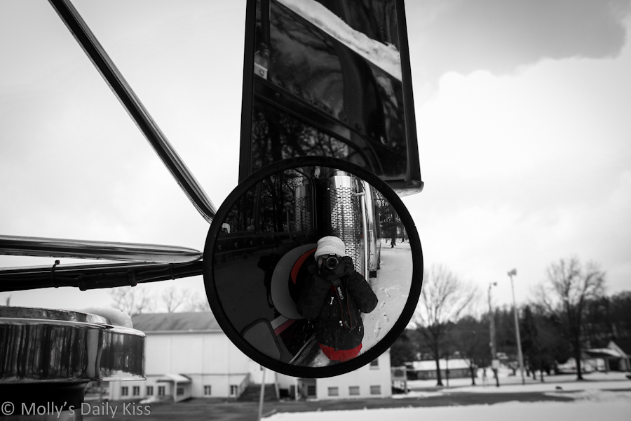 self portrait in wing mirror of truck