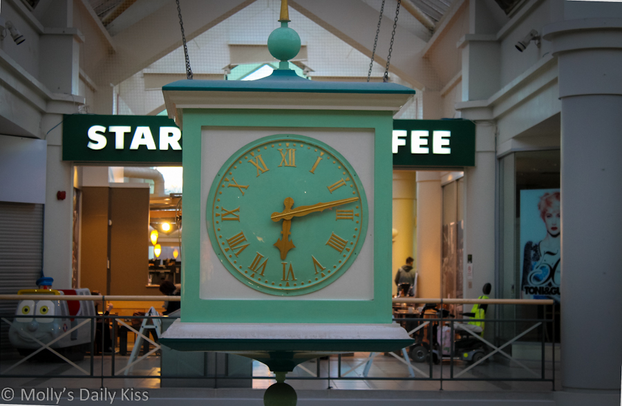 Suspended clock in front of coffee shop