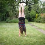 Young girl doing perfect handstand in the garden