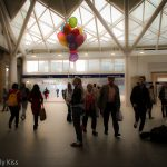 Woman with bunch of balloon in train station