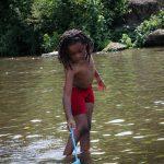 Black boy fishing in the stream