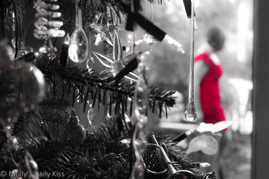 Self portrait through the Christmas tree wearing red dress
