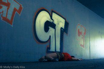 Woman laying on the ground beneath graffiti