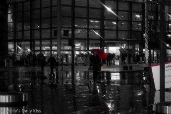 Woman with red umbrella outside Kings Cross