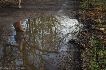 reflection in a puddle of a woman runner