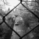 wire fence over road black and white