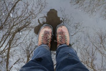 reflection of my in walking boot in a puddle