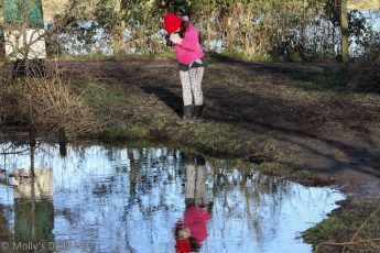 Reflection of child taking photograph