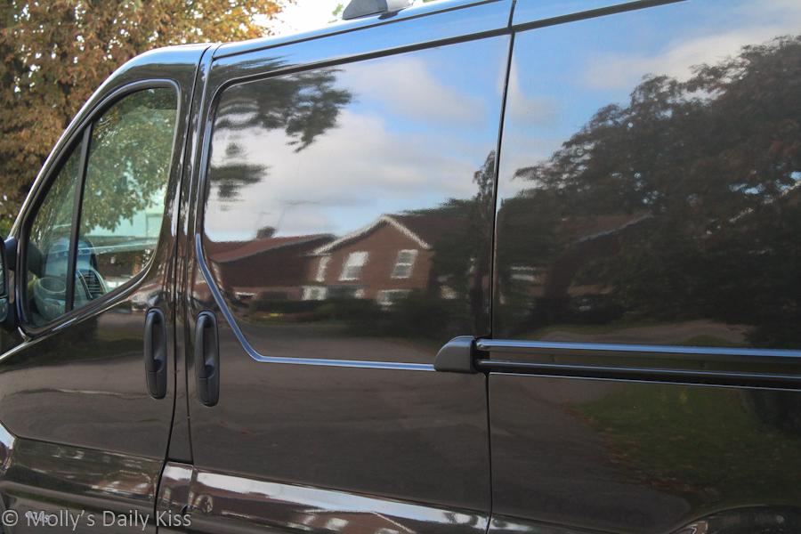 reflection of houses in black van