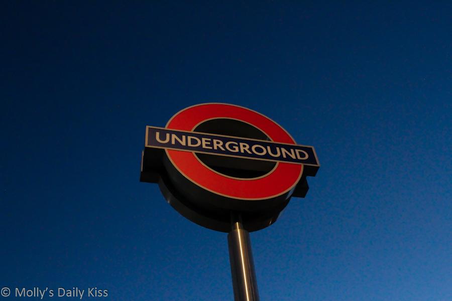 London underground sign against evening blue sky