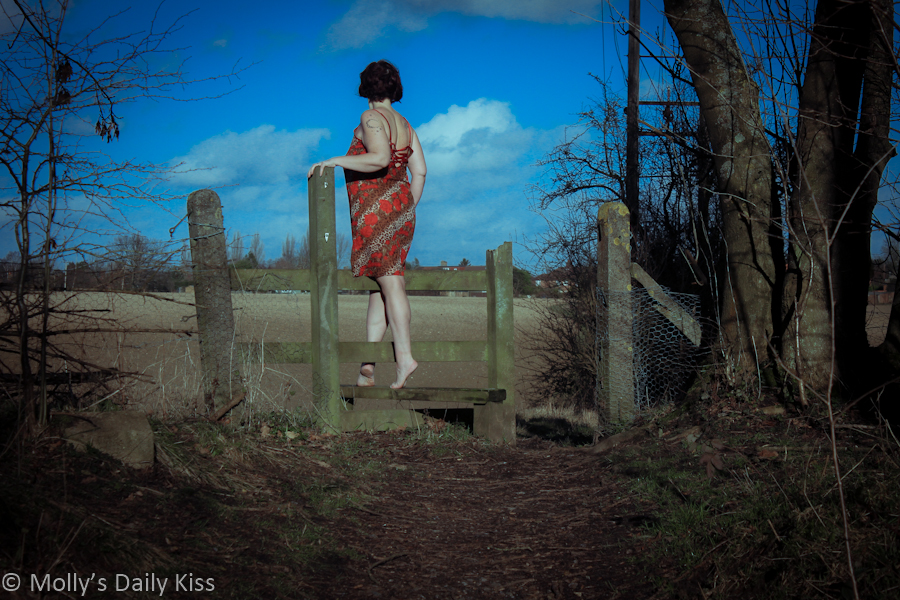 Woman stepping over stile - self portrait