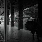 People walking in Bristol reflected in building