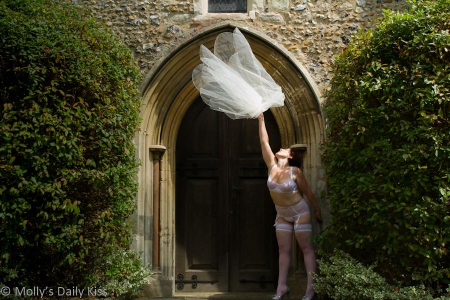 Bride thoring away her veil outside church