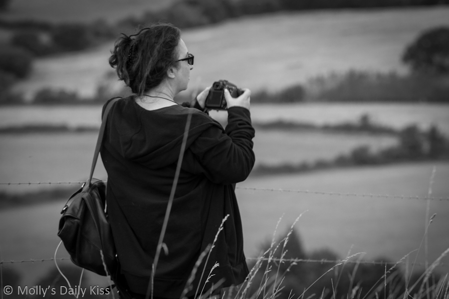 Woman taking photograph in black and white