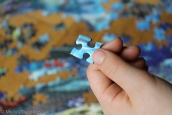 child holding piece of puzzle