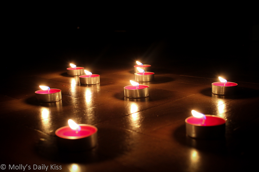 Tealight candles relfected in wooden floor