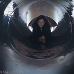 Girl looking down slide tunnel