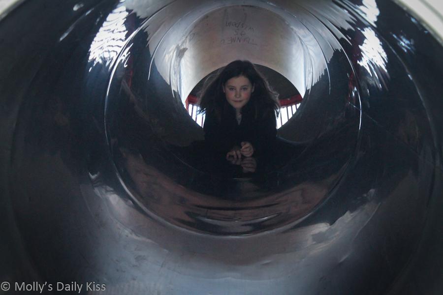 Girl looking down slide tunnel