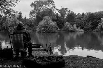 Fisherman sitting alone on bank of pond