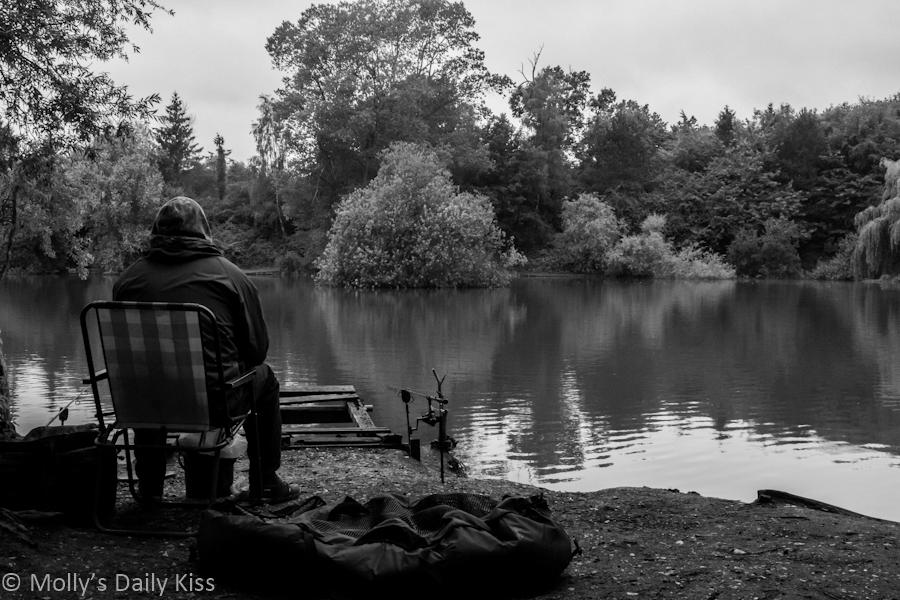 Fisherman sitting alone on bank of pond