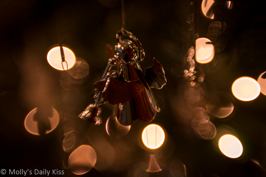 Angel on Christmas tree surrounded by bokeh