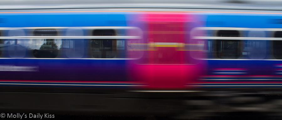 Blurred train rushing through station