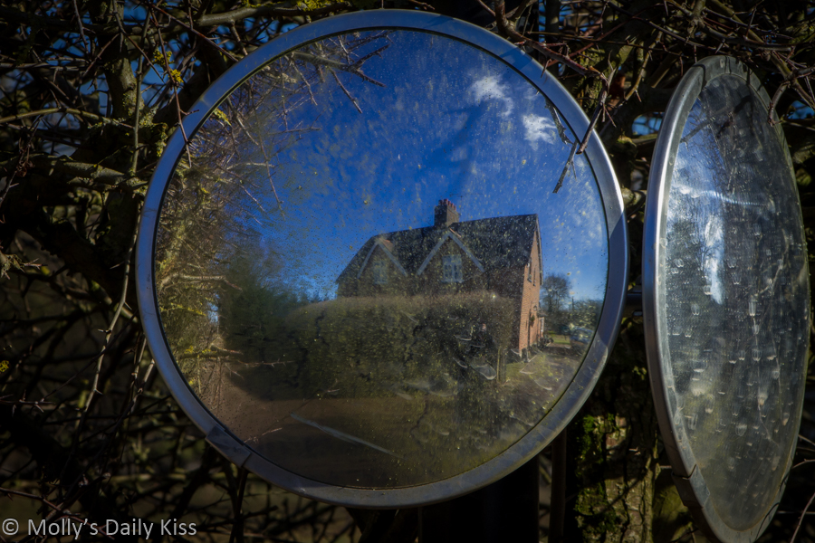 Road mirror with house reflected in it