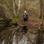 Woman sitting by woodland pond