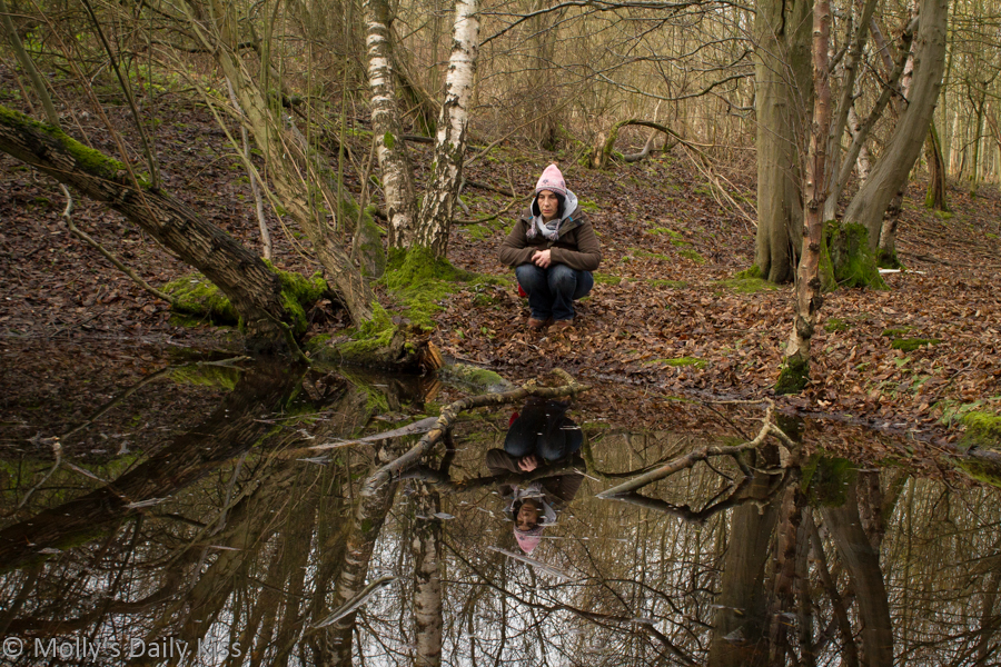 Woman sitting by woodland pond