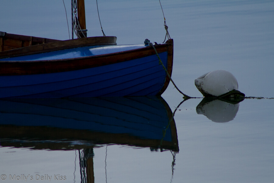 Reflection of row boat and bouy in the water
