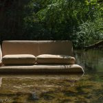 Abandoned sofa in a river
