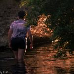 Young man walking in the river Mimram