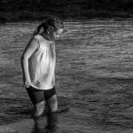 girl playing in river in sunlight