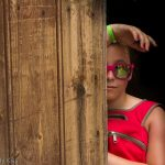 Girl peeking round door with reflection in her sunglasses