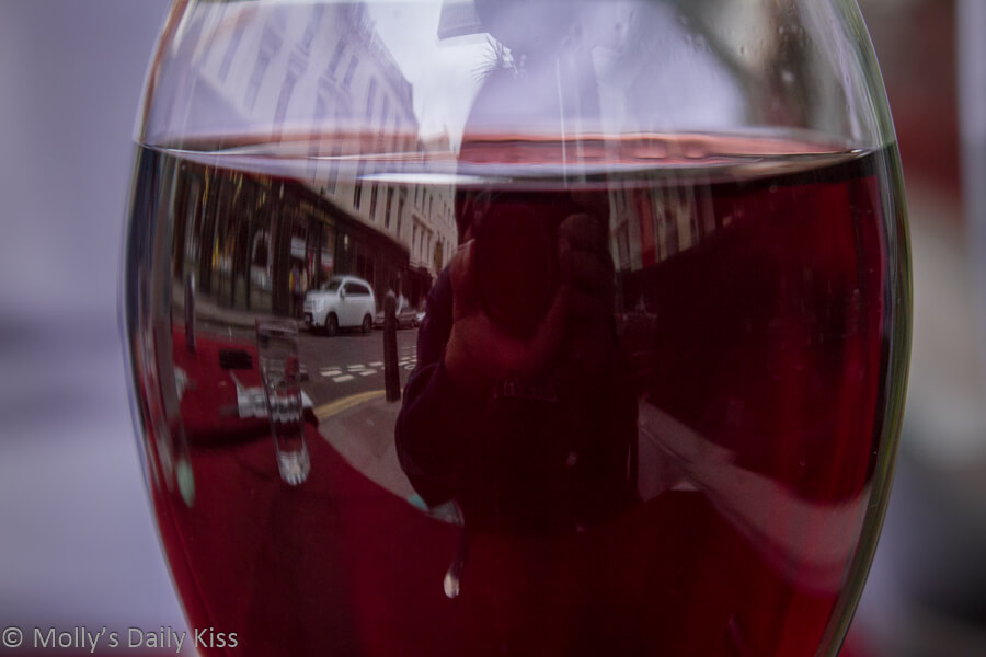 Street reflection in glass if red wine