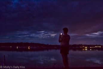 Boy taking photo of sunset night sky