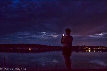 Boy taking photo of sunset night sky