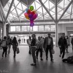Woman with coloured balloons in Kings Cross Station