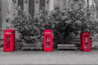 Three red London telephone boxes lined up in a row