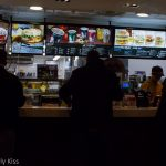 Silhouettes of people waiting at fast food counter