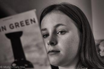 Black and white of Girl reading John Green book